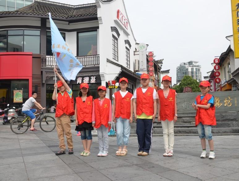 """慈溪志愿者""""字样的红色帽,身穿红色志愿者马甲,像一个个可爱的小精灵"""
